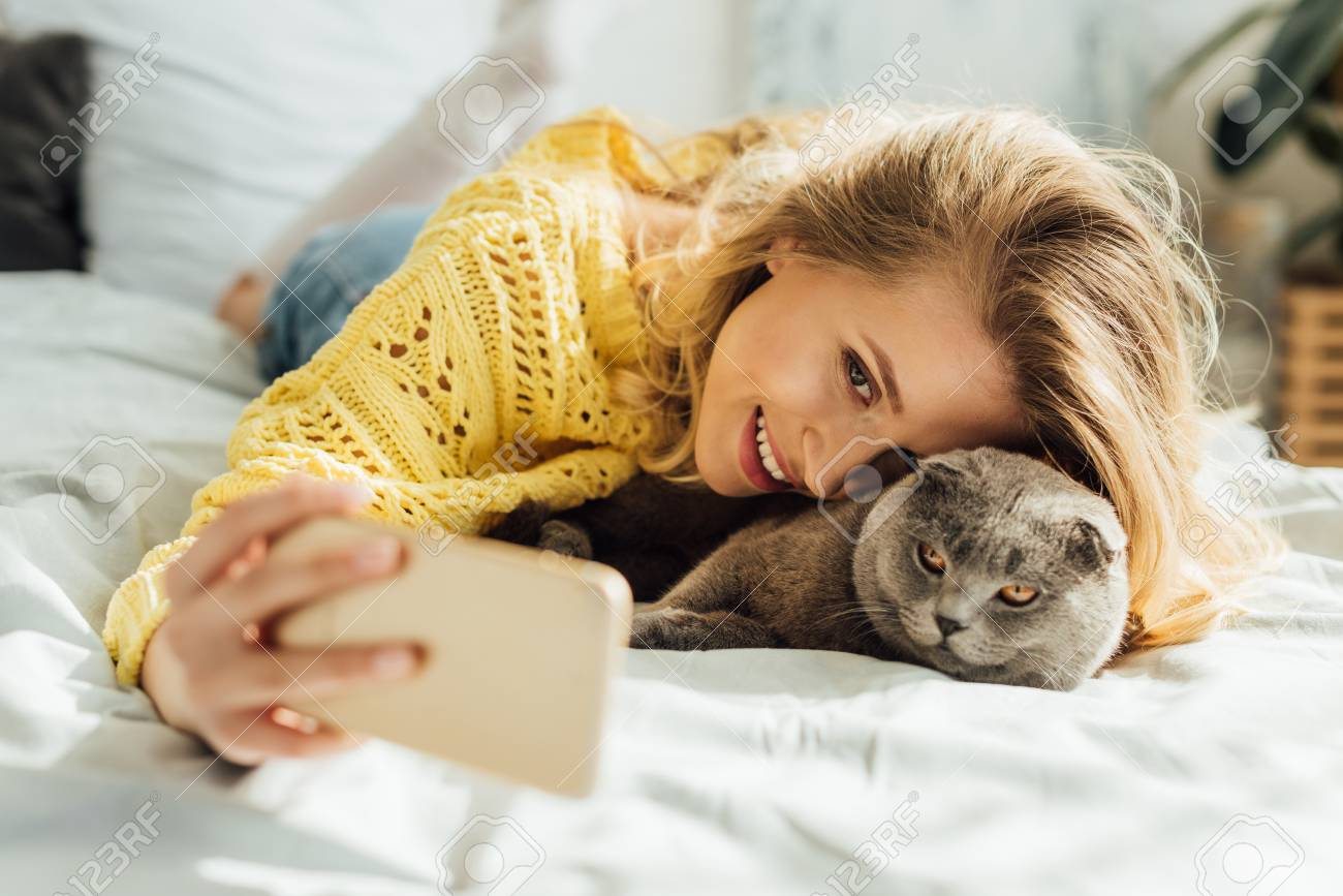 beautiful smiling young woman taking selfie on smartphone while lying in bed with scottish fold cat - 120206385