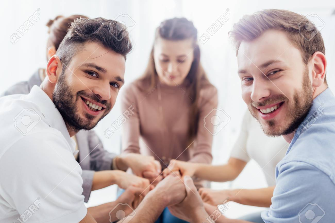 group of people sitting, smiling and stacking hands during therapy session - 120077033