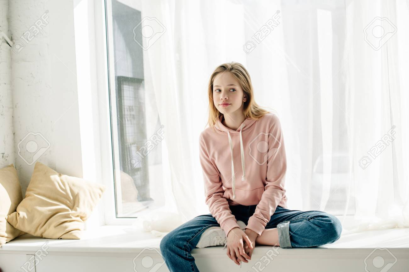 Pensive teenage kid in jeans sitting on window sill and looking away - 120874869