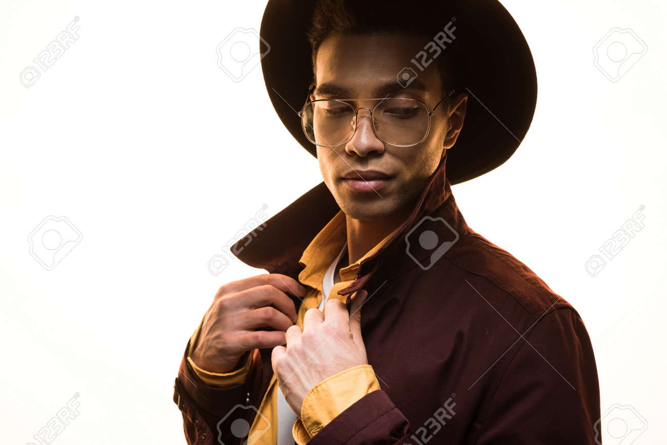Stylish mixed race man in glasses and hat adjusting coat and posing isolated on white background - 120875773