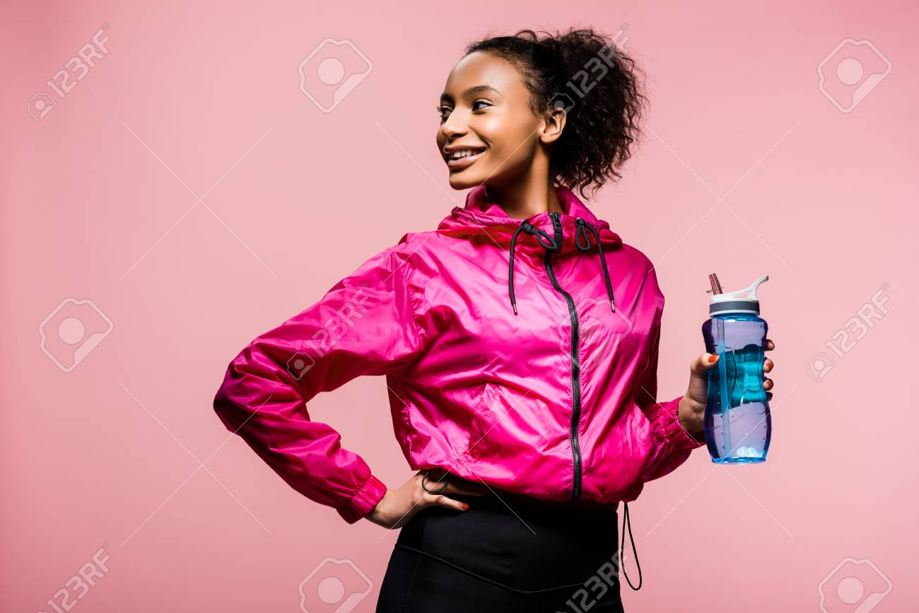 beautiful smiling african american sportswoman with sport bottle isolated on pink - 121417794