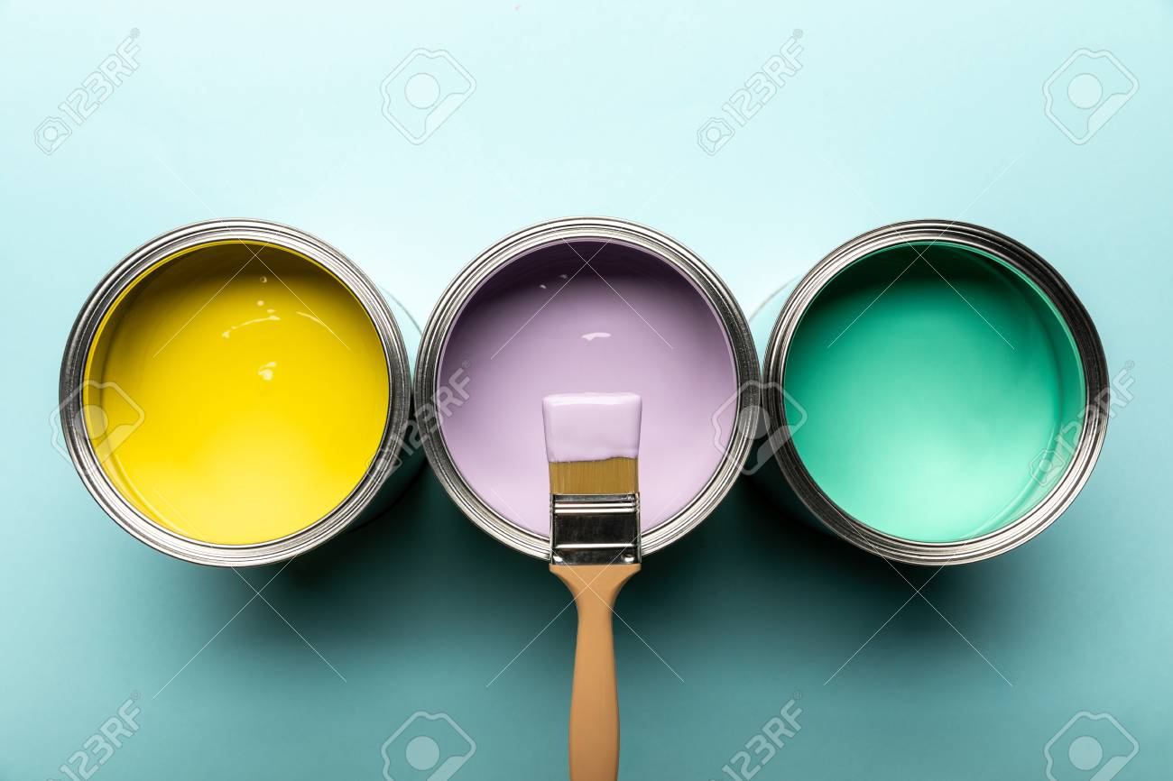 Top view of three tins with paints and brush on blue surface - 122292121