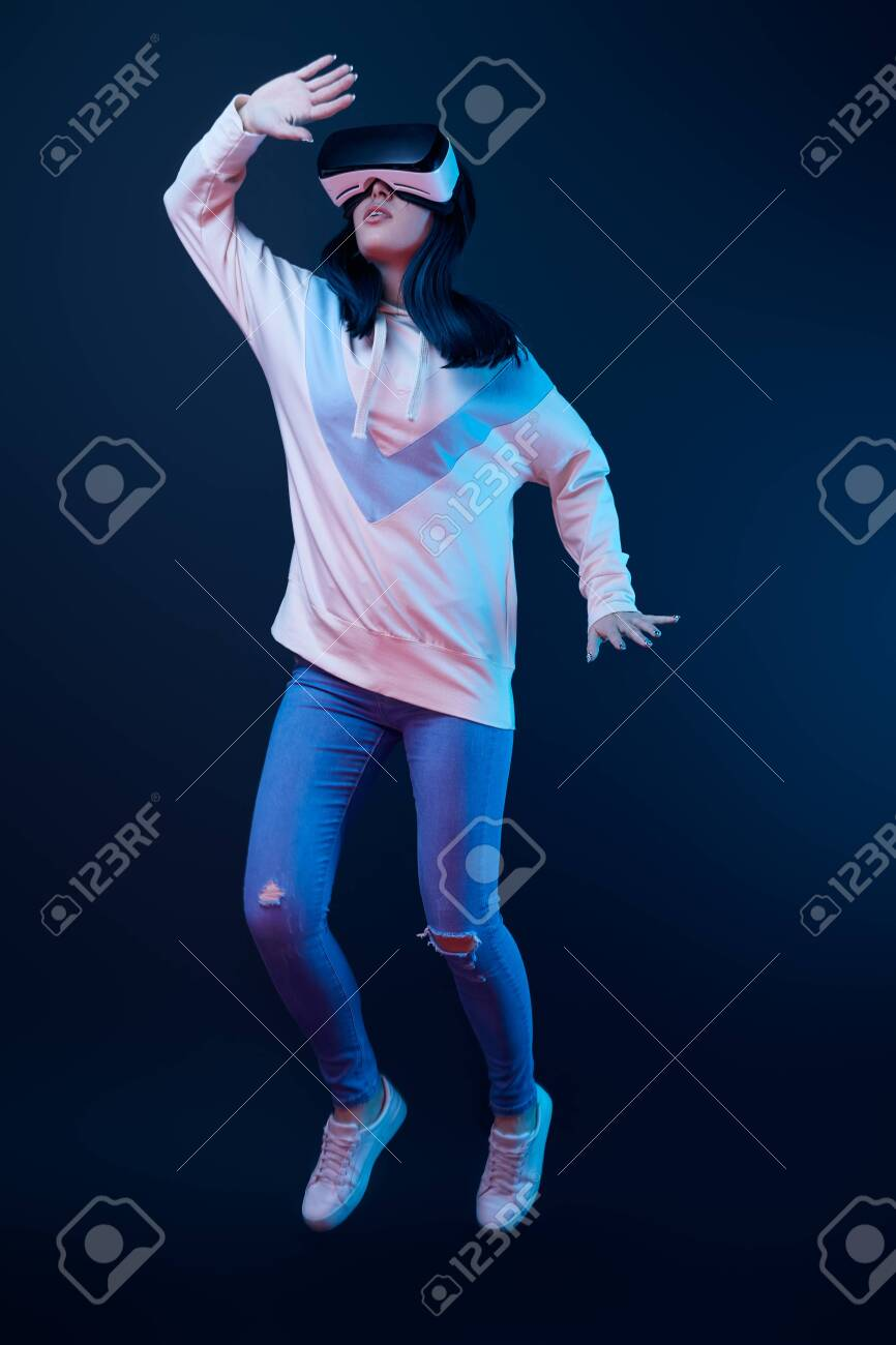 Young woman gesturing while using virtual reality headset and jumping on blue background - 122293018