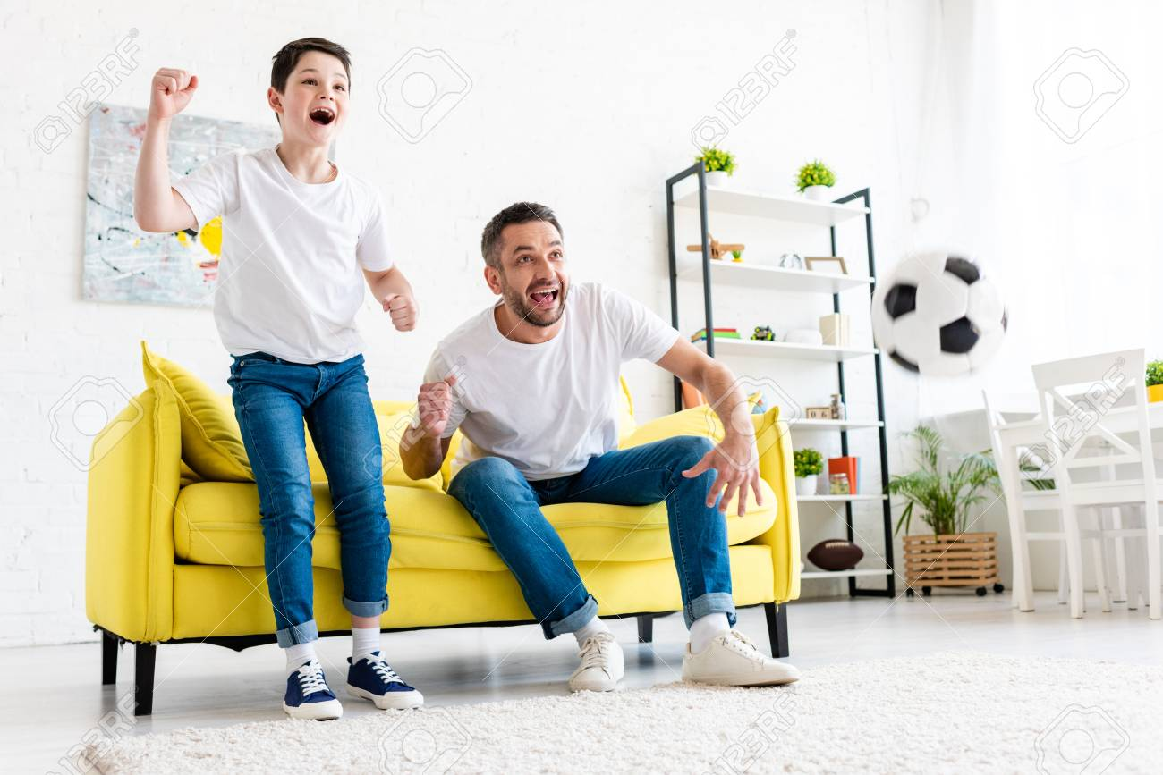 Excited father and son cheering while watching sports match in Living Room - 123309607
