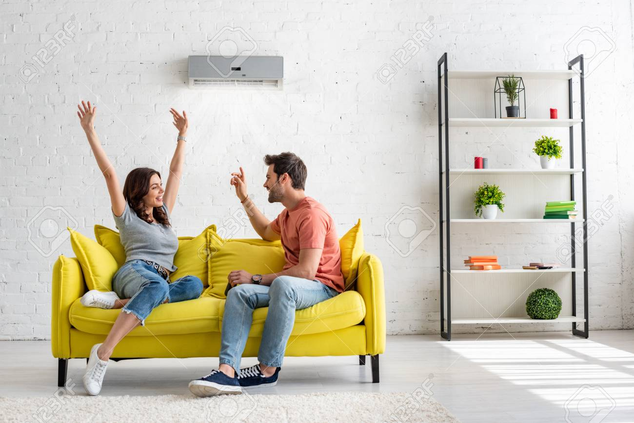 Happy man and woman talking while sitting on yellow sofa under air conditioner at home - 123532042