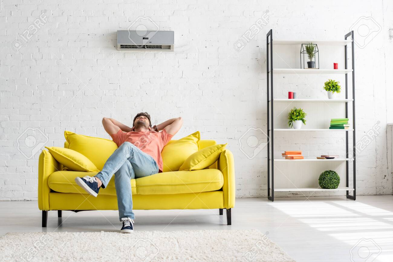 Young man sitting on yellow sofa under air conditioner in spacious apartment - 123533082