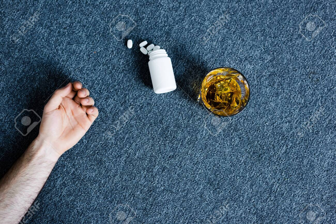 Cropped view of man lying on grey floor near glass of whiskey and container with pills - 123533457