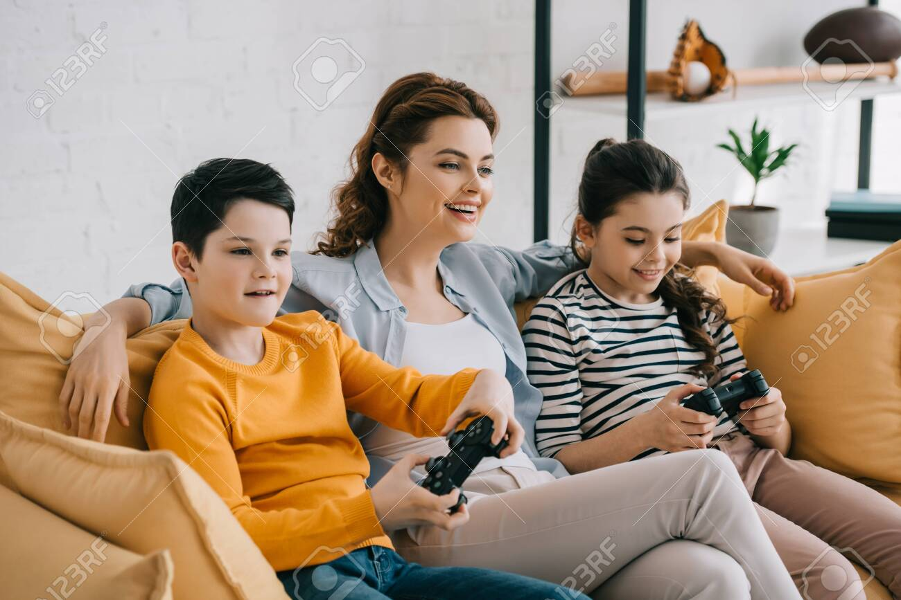 happy smiling woman sitting on yellow sofa near children playing video game with joysticks - 123585425