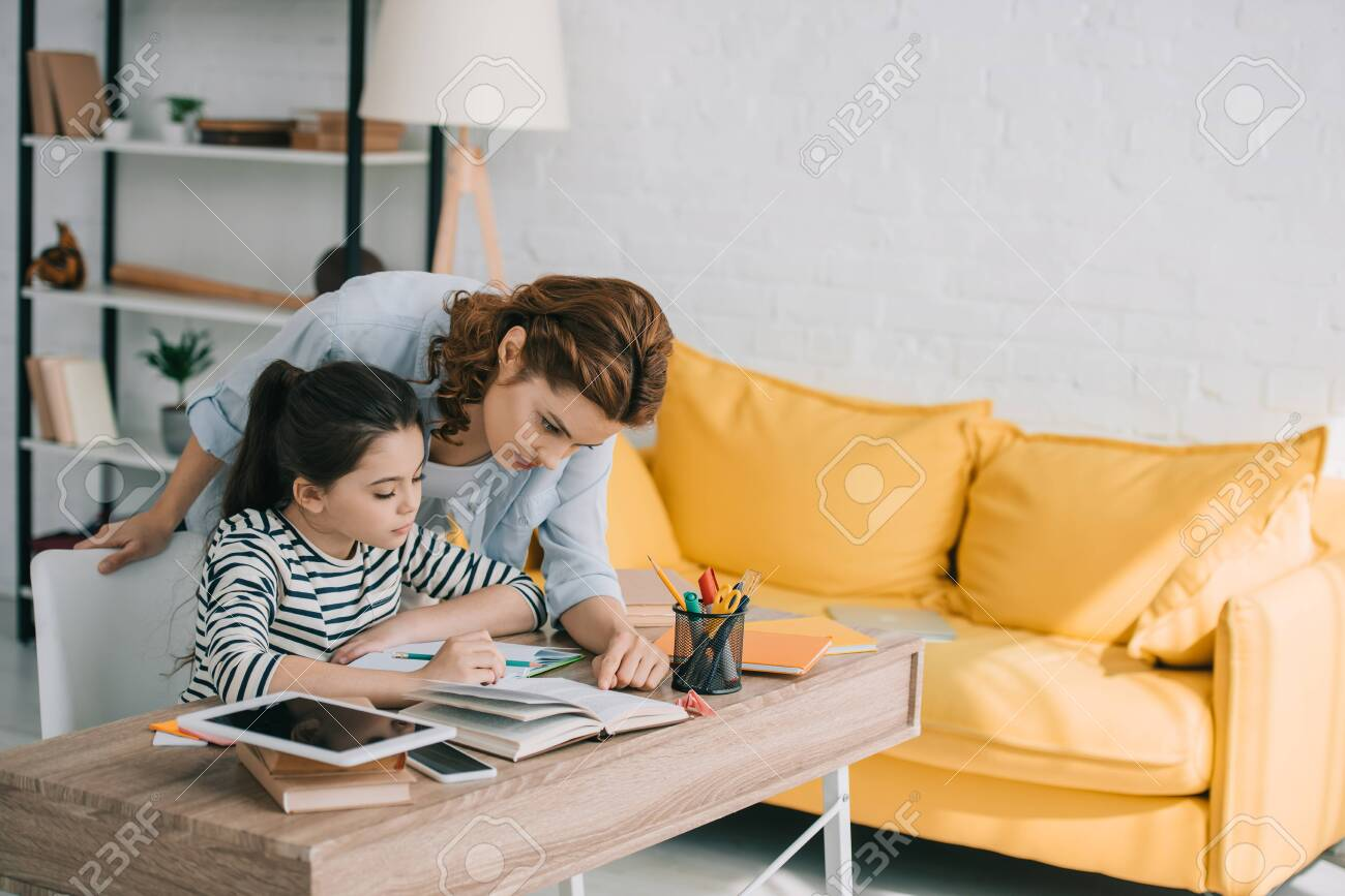 beautiful woman helping adorable daughter doing schoolwork at home - 123628475