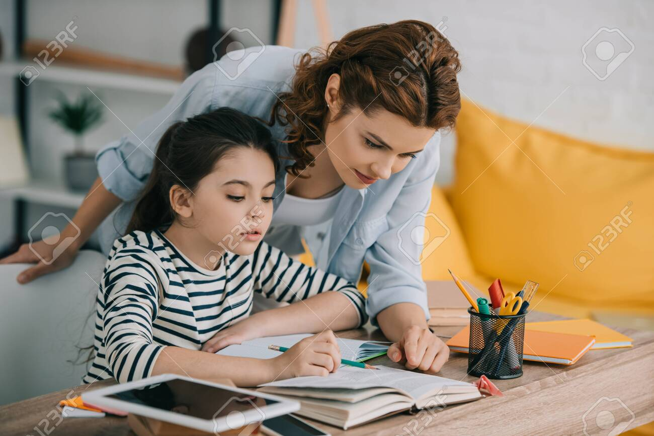 attentive mother helping adorable daughter doing schoolwork at home - 123665330