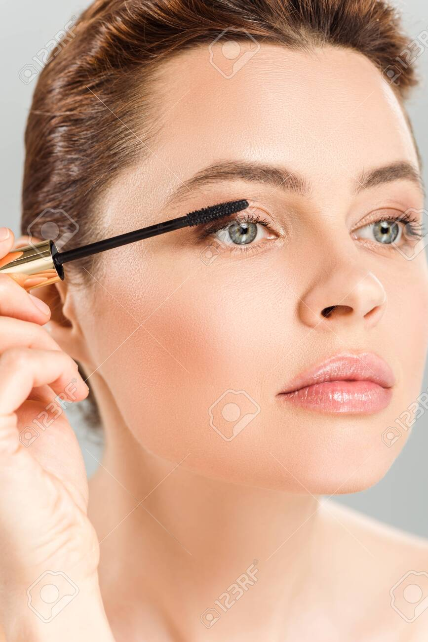 Attractive woman applying mascara isolated on grey background - 124712901
