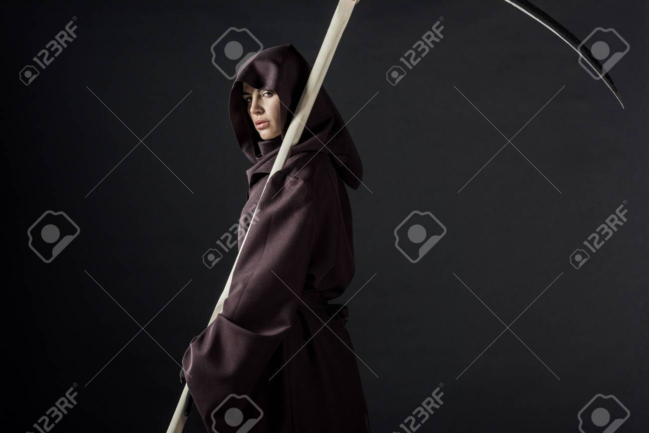 Woman in death costume holding scythe and looking at camera isolated on black background - 125073223