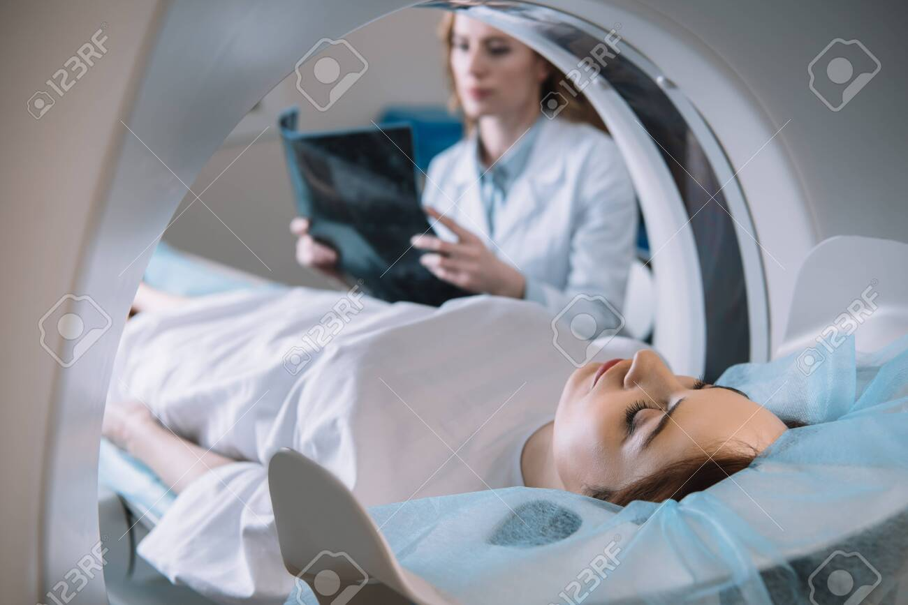 Selective focus of radiologist holding x-ray diagnosis while patient lying on ct scanner bed during diagnostics - 125221853