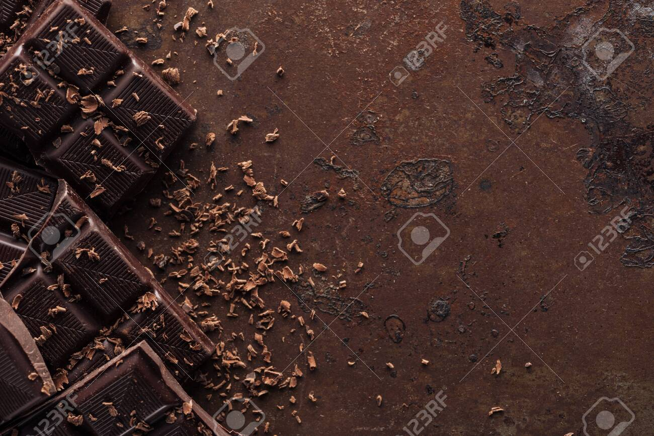 Pieces of chocolate bar with chocolate chips on metal background - 125322840