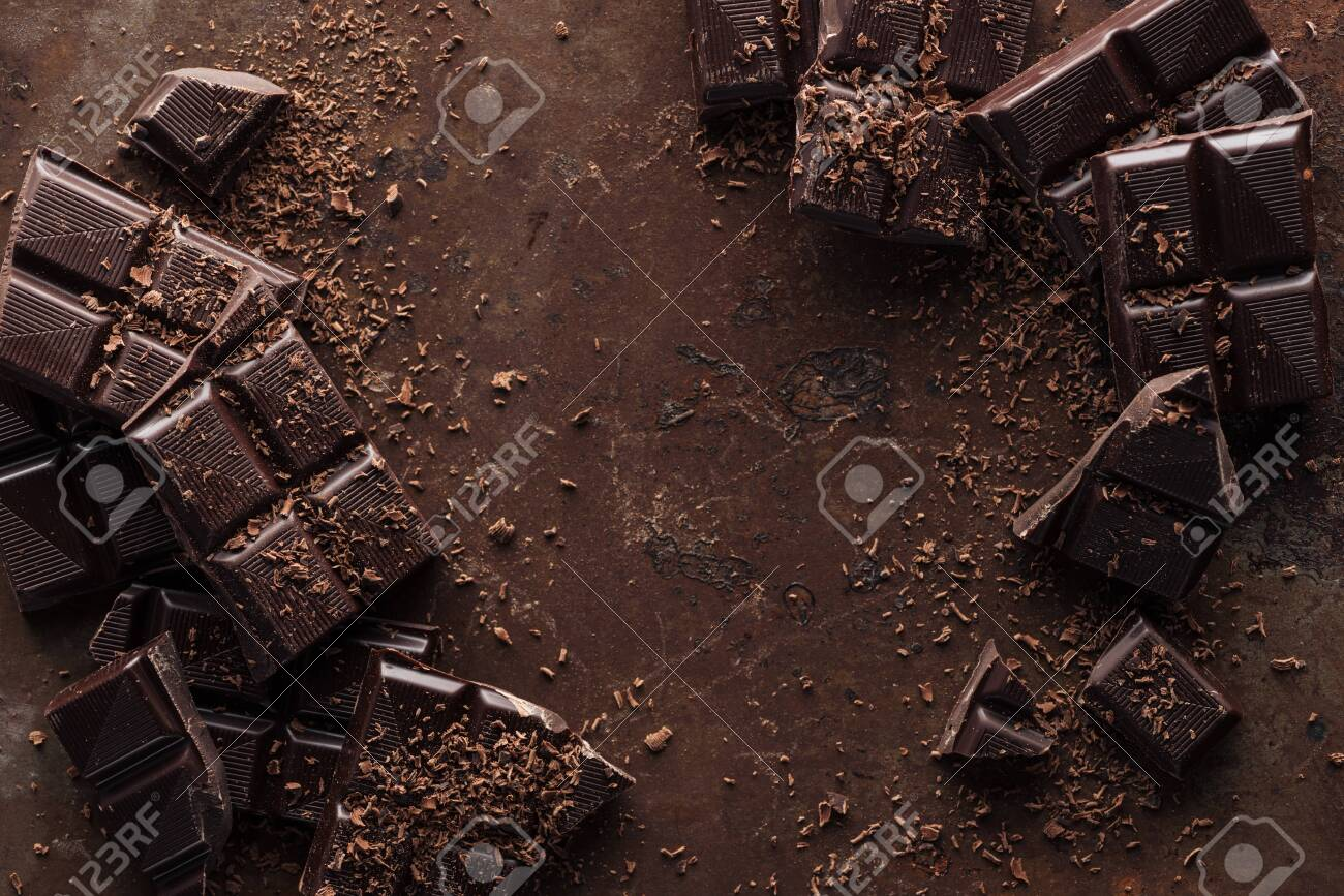Top view of pieces of chocolate bar with chocolate chips on rust metal background - 125362678