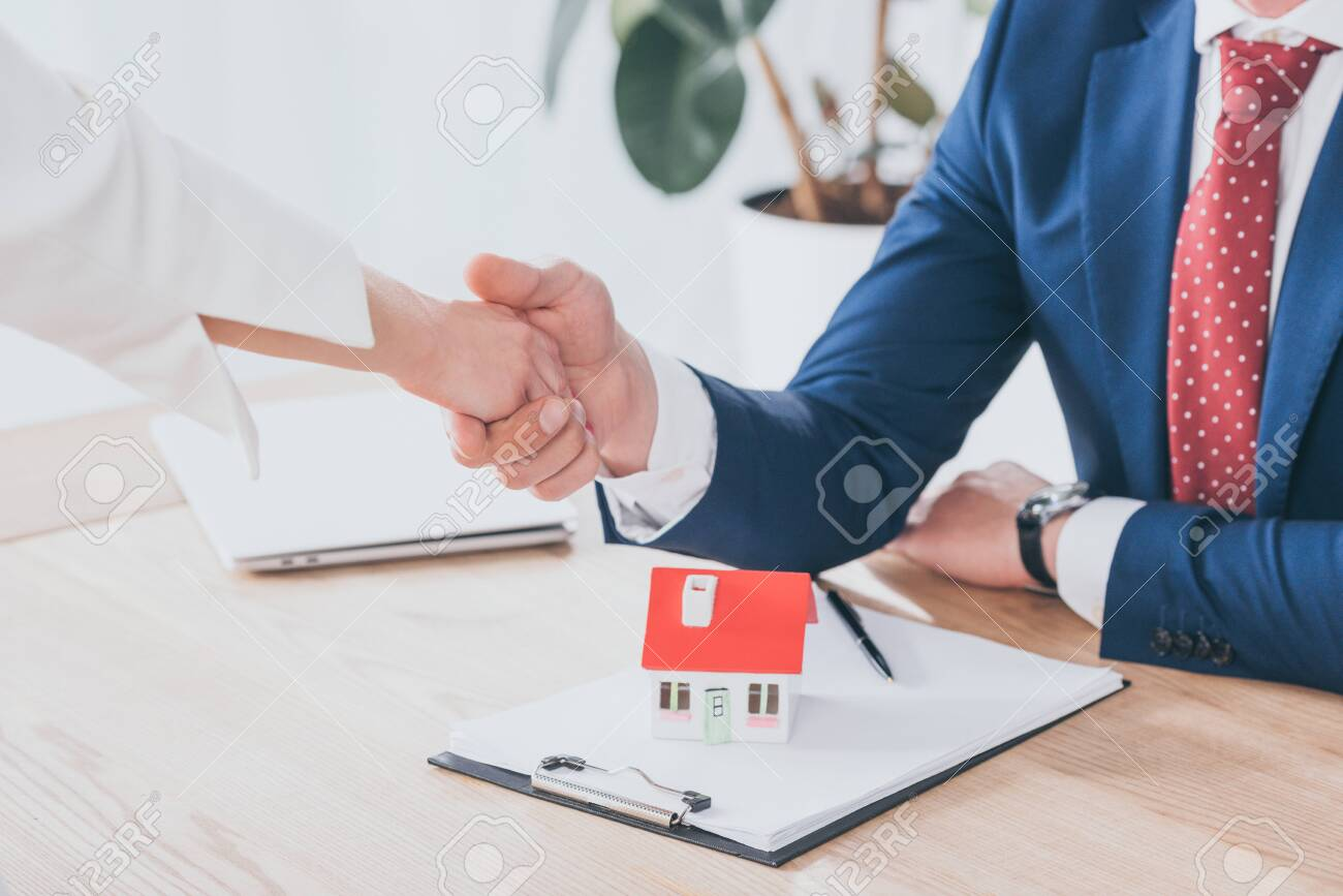 partial view of businessman and client shaking hands near house model on table - 125399373