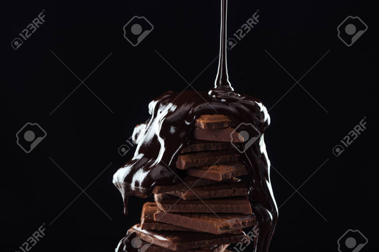 Hot melted chocolate pouring on chocolate stack, isolated on black - 125404063