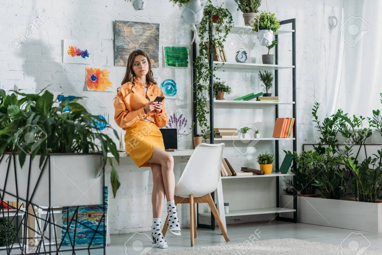 stylish grl using smartphone in spacious room decorated with green plants and colorful paintings on wall - 125404523