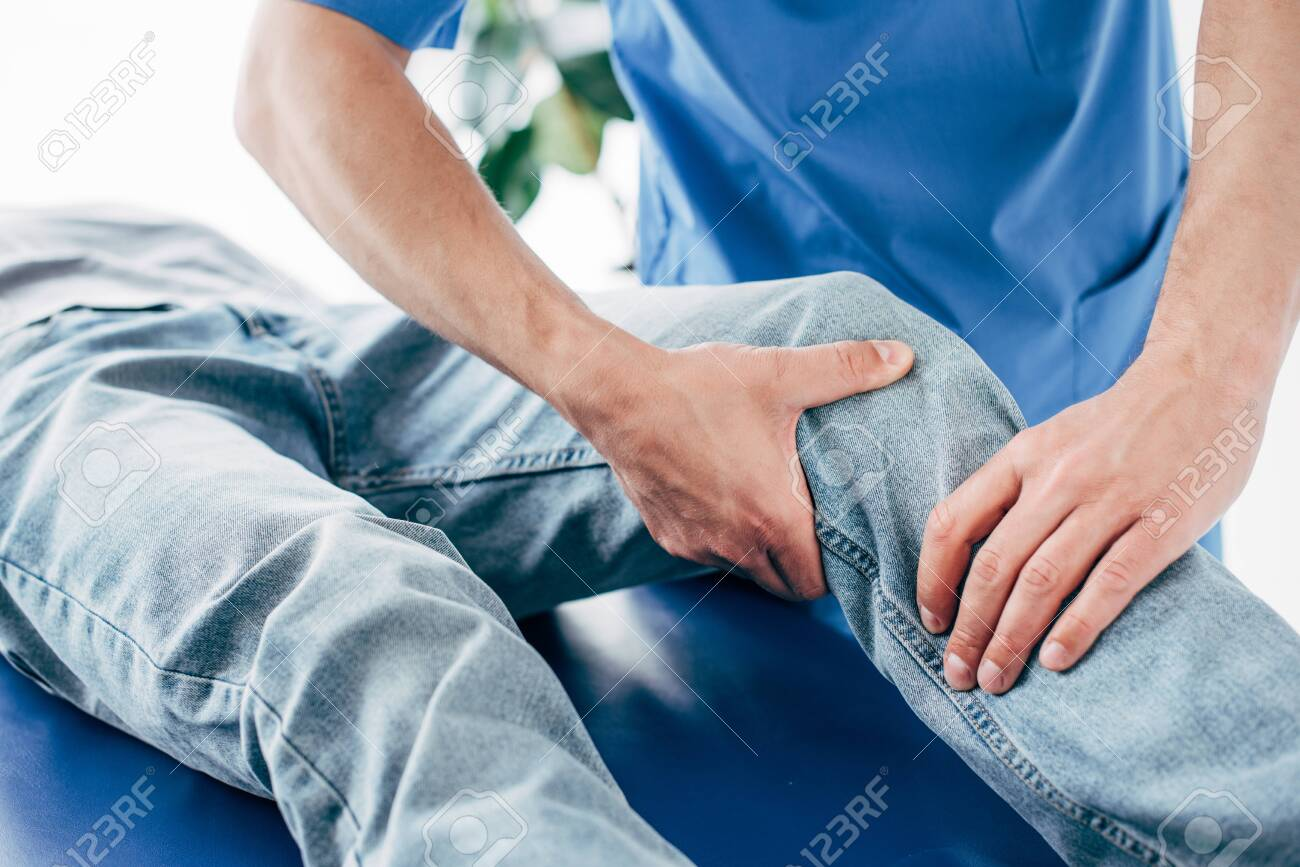 Cropped view of chiropractor massaging leg of patient in hospital - 125526455