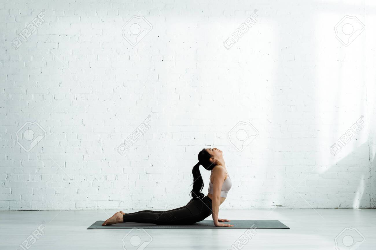 Pretty Asian woman doing exercise on yoga mat - 125526719