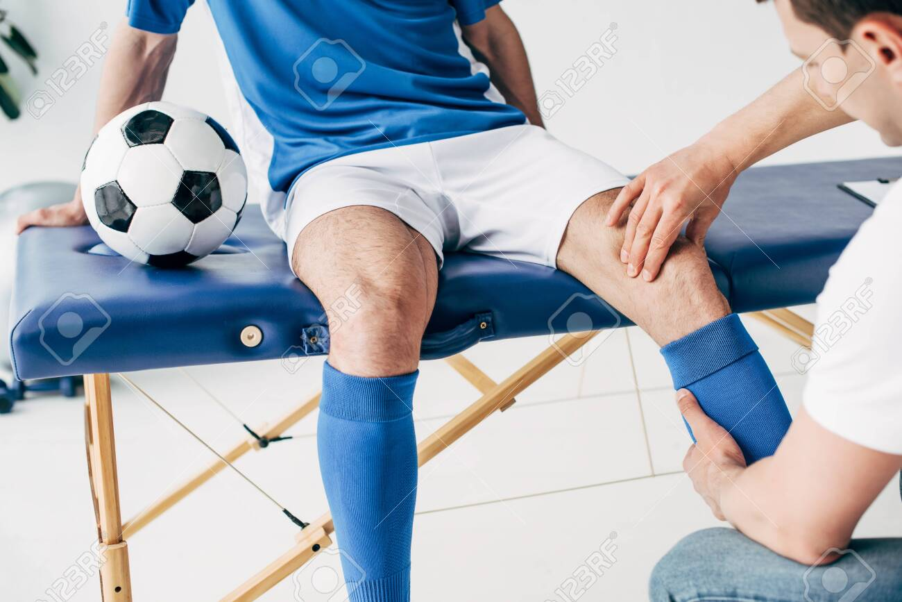 Partial view of Physiotherapist massaging leg of football player in hospital - 125527962
