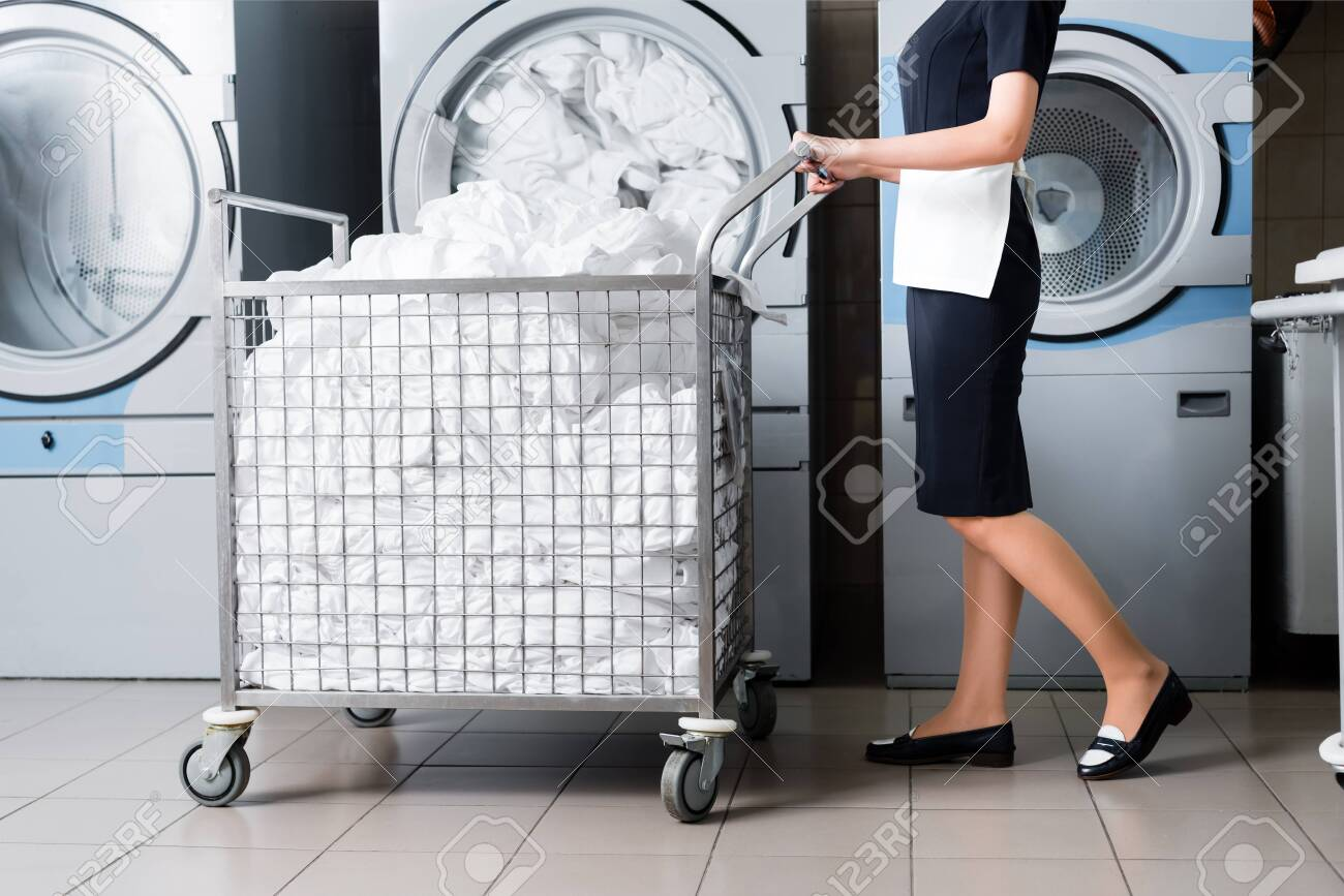cropped view of housemaid standing near cart with bedding in laundry - 126285433