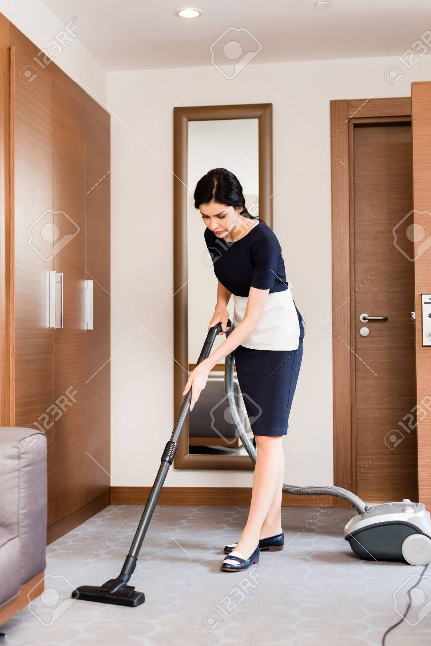 brunette housemaid cleaning carpet with vacuum cleaner in hotel room - 126285743