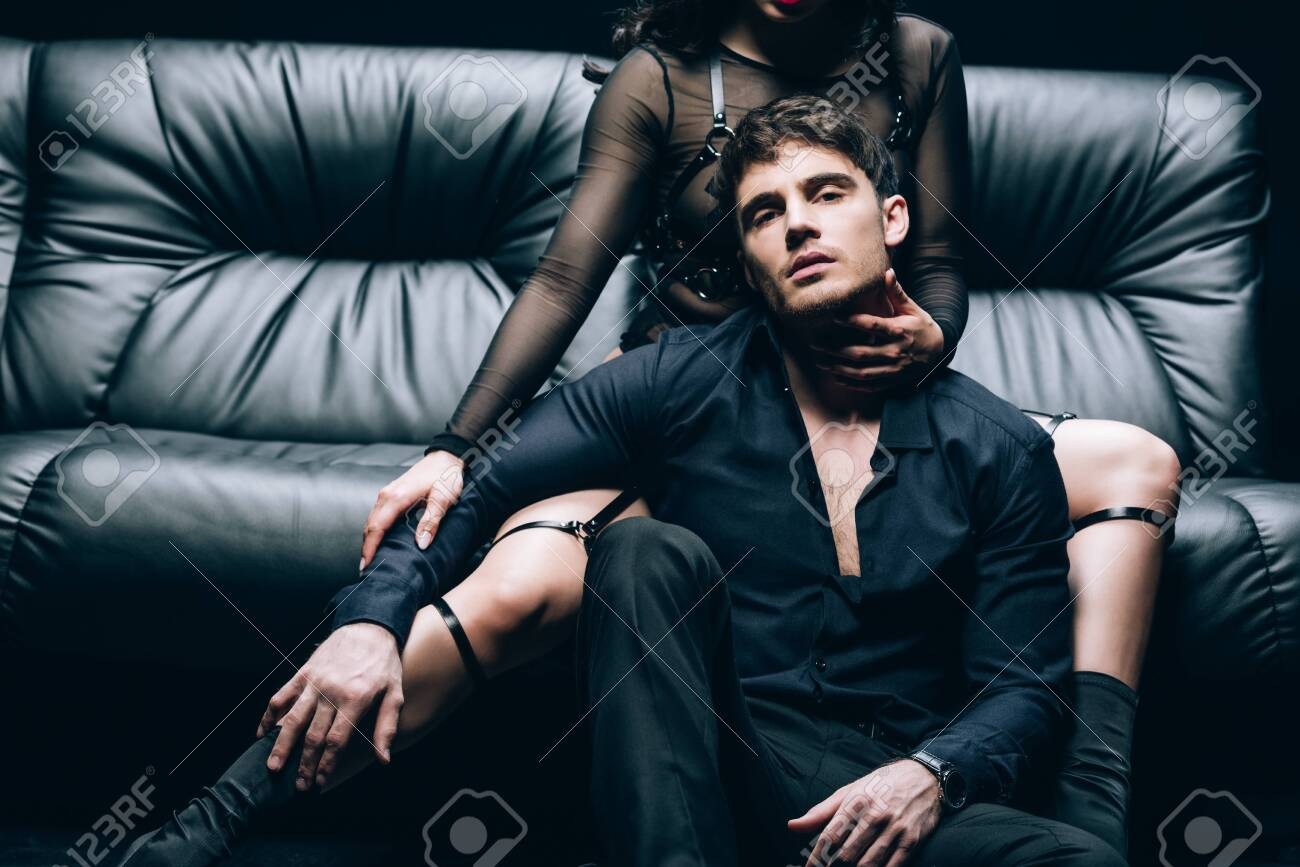 Passionate handsome man sitting near woman in costume on black leather sofa - 126296525