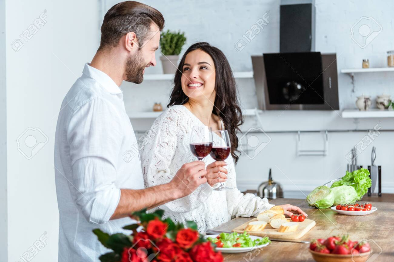 Happy man clinking glasses of red wine with smiling woman at kitchen - 127543654
