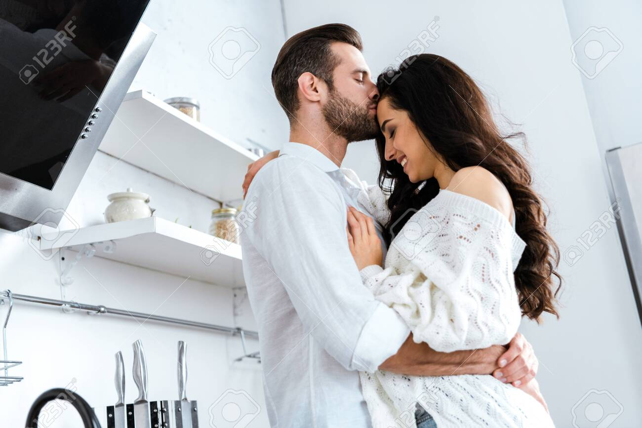 Man with closed eyes gently hugging and kissing woman - 127543721