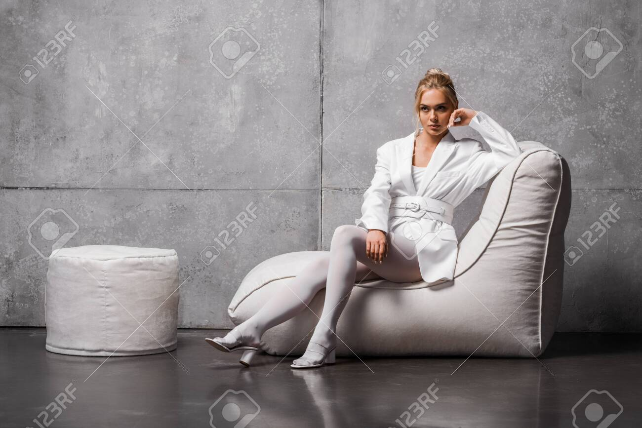 Astounding Pensive Young Woman Sitting On Soft Bean Bag Chair On Grey Andrewgaddart Wooden Chair Designs For Living Room Andrewgaddartcom
