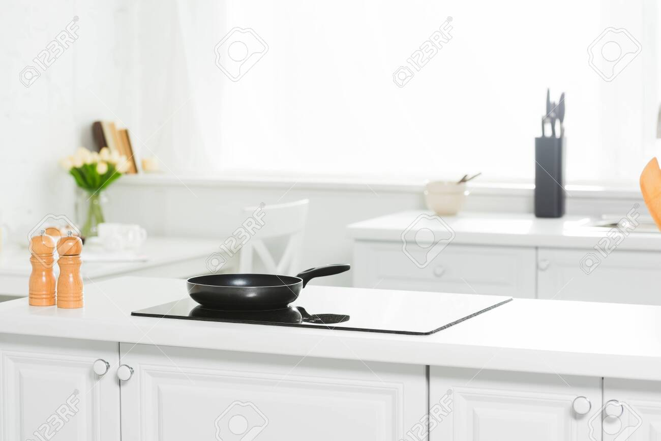 modern kitchen with white counter, cooker and frying pan - 128083936