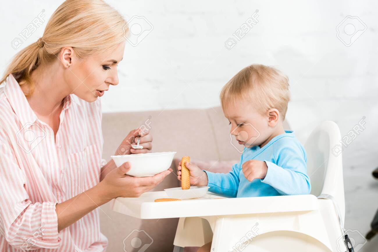 Attractive Mother Holding Spoon With Baby Food Near Cute Toddler