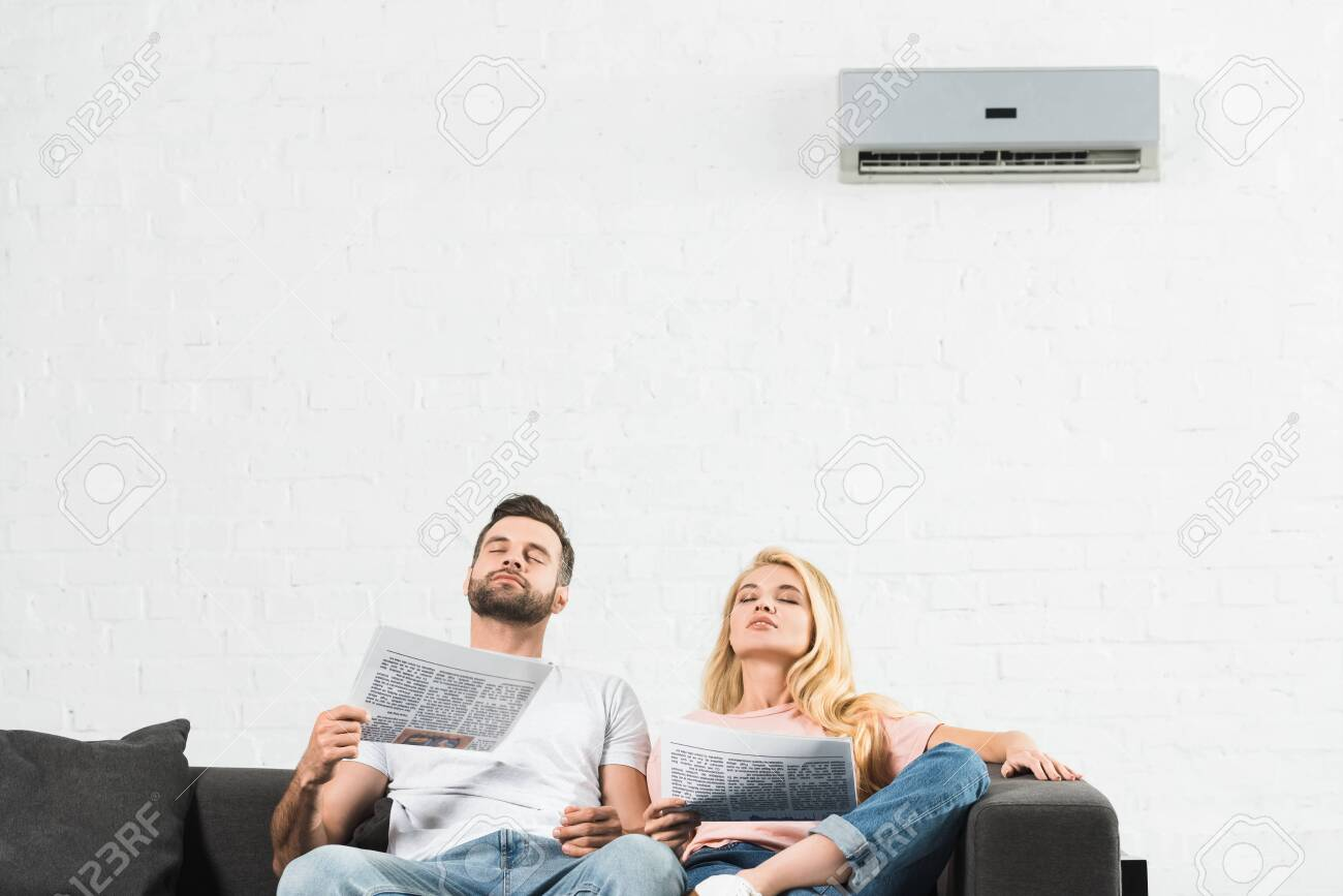 couple on couch with newspapers suffering from heat under air conditioner at home - 128084313