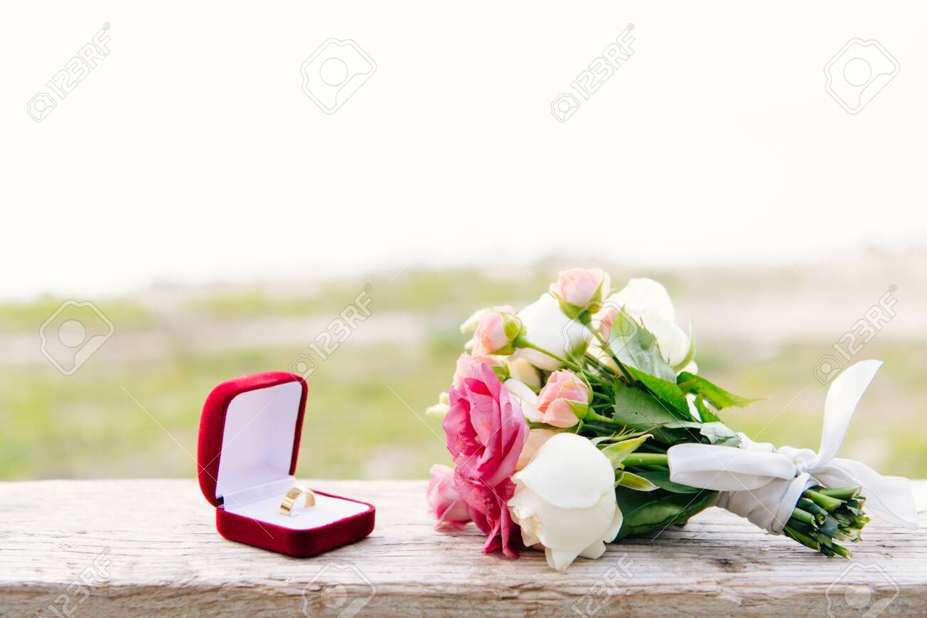 wedding ring in red box and bouquet on wooden surface - 128144500