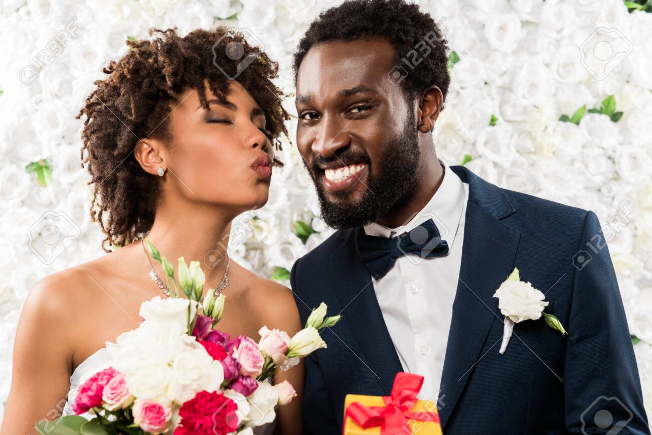 african american bride with duck face holding bouquet with flowers near cheerful bridegroom - 128144418