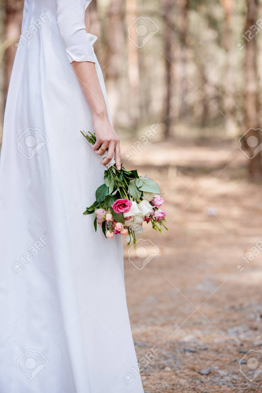 cropped view of bride in white attire holding wedding bouquet in forest - 128145206