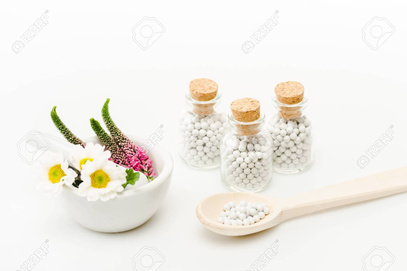 flowers in mortar near pestle and glass bottles with pills on white - 128146342