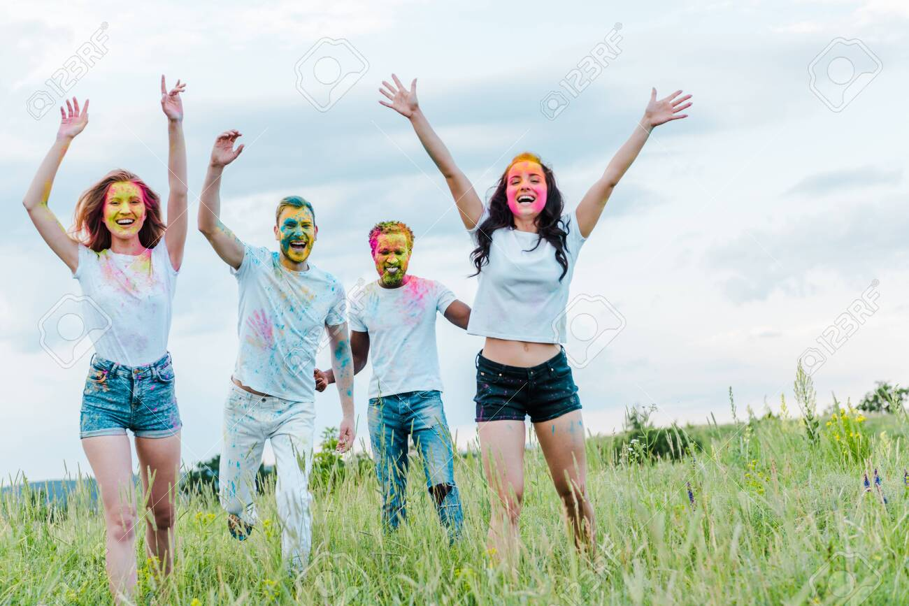 happy multicultural friends with colorful holi paints on faces gesturing while standing outside - 128287940