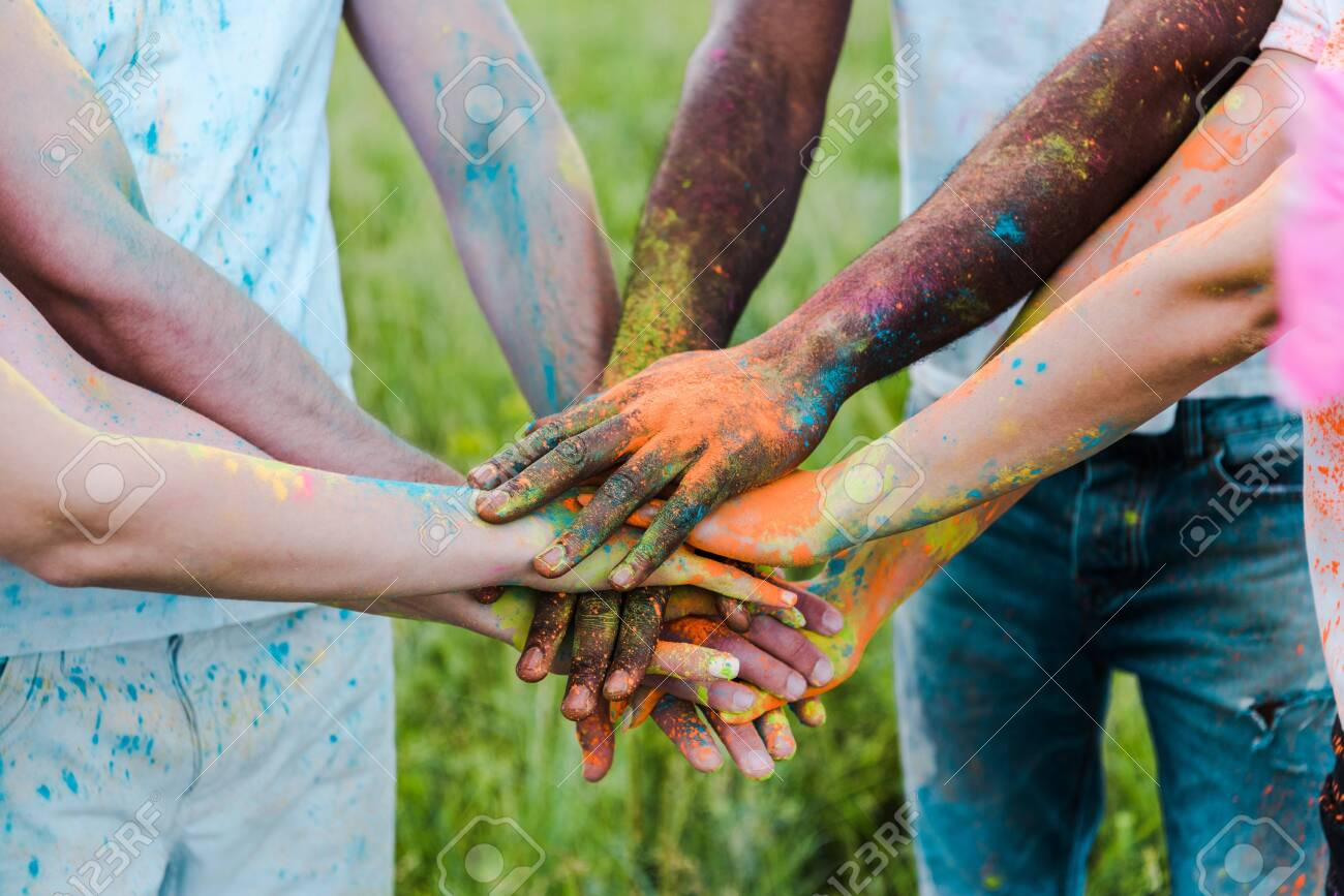 cropped view of multicultural friends with colorful holi paints putting hands together - 128186026