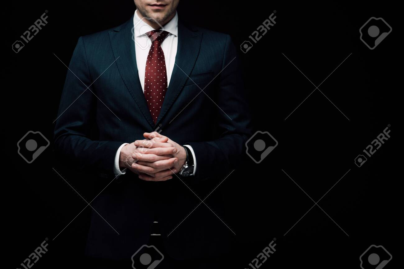 partial view of confident businessman standing with clenched hands isolated on black, human emotion and expression concept - 128147259