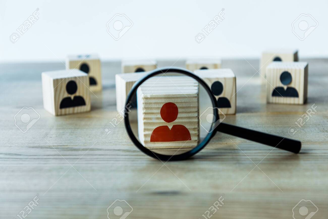 selective focus of magnifying glass near cubes on wooden desk - 128157261