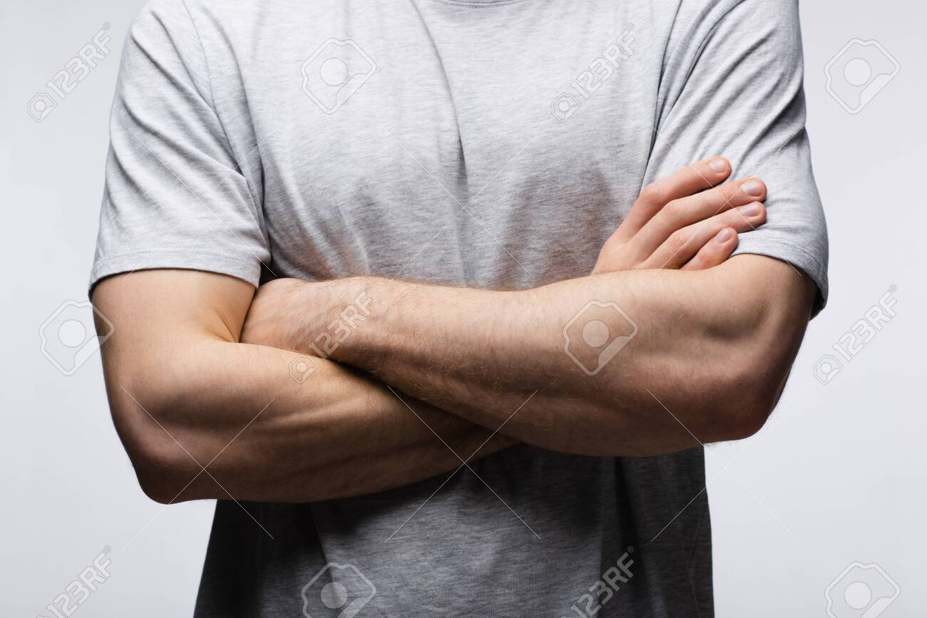 cropped view of man standing with crossed arms isolated on grey, human emotion and expression concept - 128157739