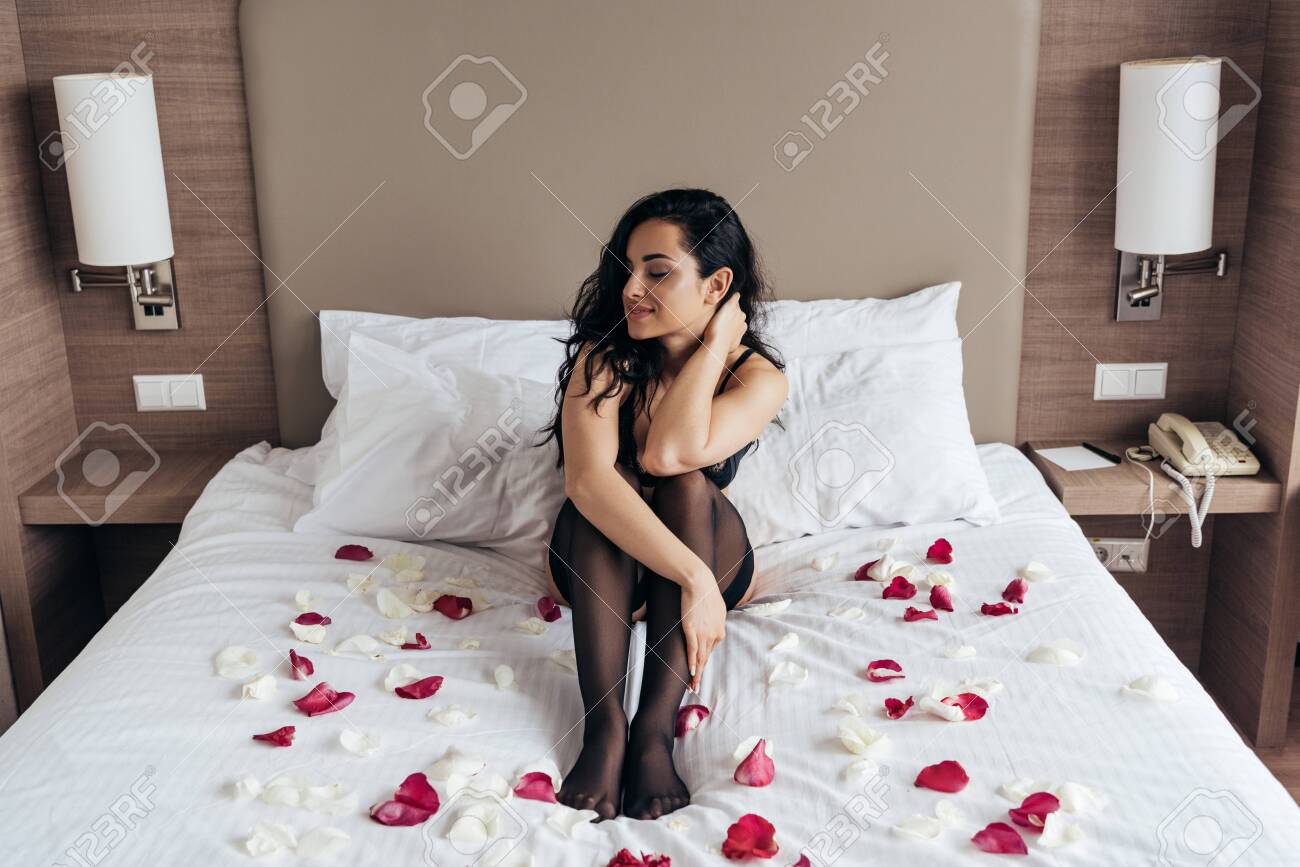 brunette girl in black stockings sitting on bed with rose petals in bedroom - 128157757