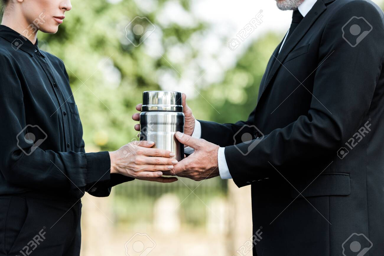 cropped view of senior man and woman holding mortuary urn - 130106329