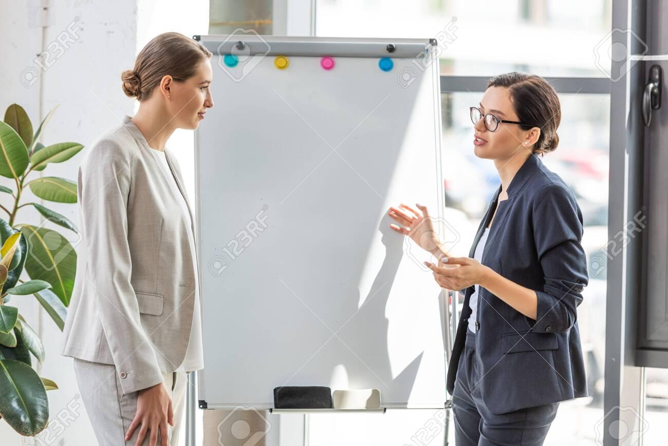 two businesswomen in formal wear standing near flipchart in office - 130333935