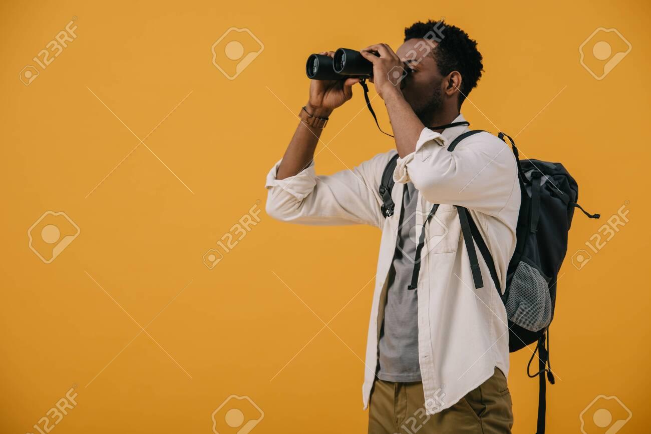 african american man looking through binoculars isolated on orange - 130335953