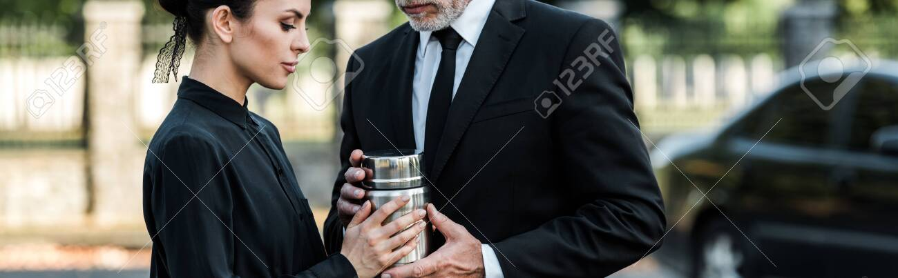 panoramic shot of man and woman holding mortuary urn - 130484971