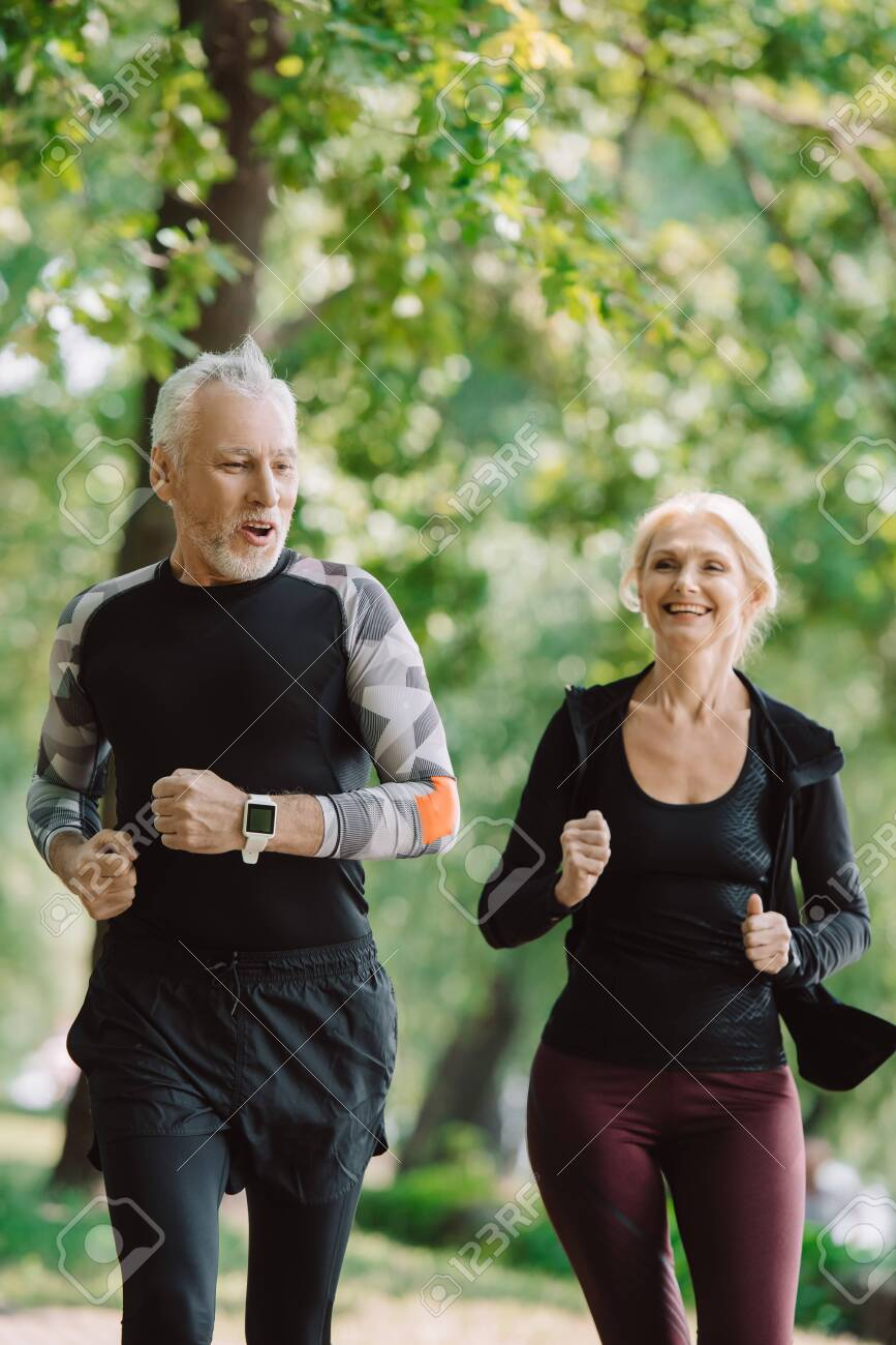 cheerful mature sportsman and sportswoman running together in park - 130486280