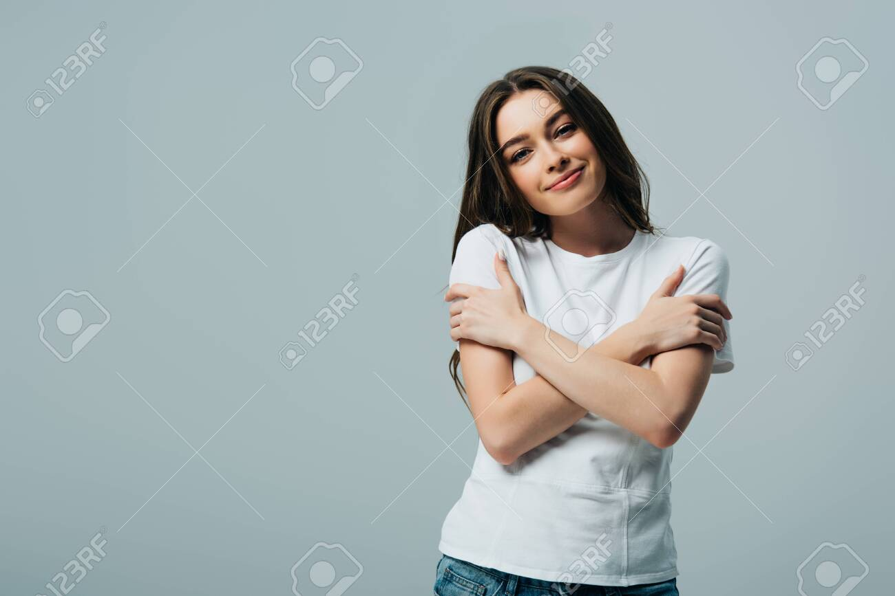 dreamy smiling beautiful girl in white t-shirt hugging herself isolated on grey - 130321814